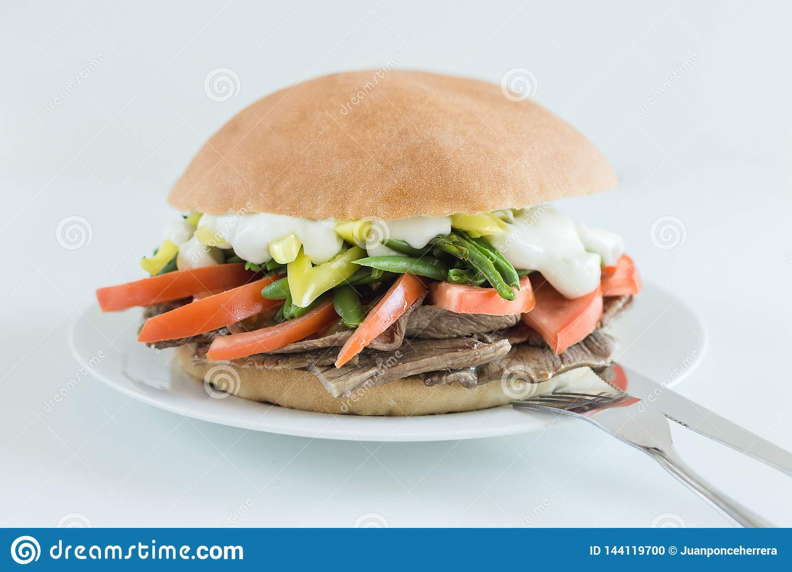 Meat sandwich with tomato, green beans, chili and mayonnaise with white background