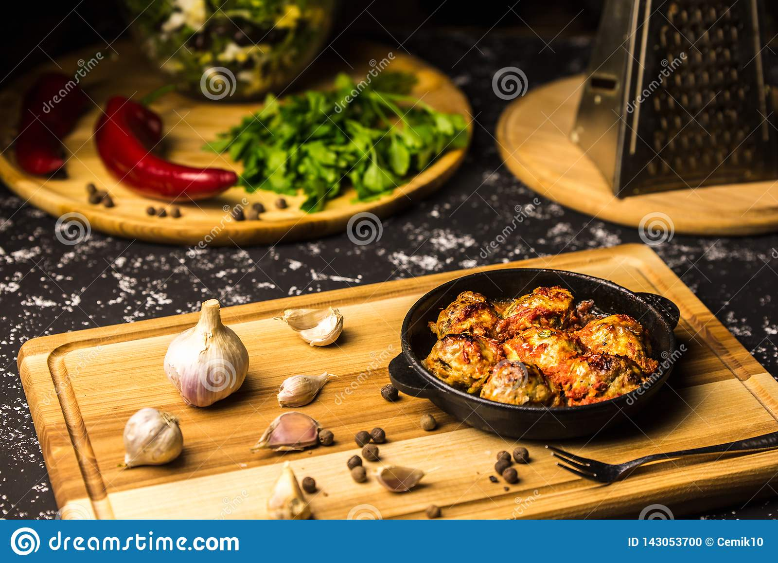 Meatballs in an iron pan on a wooden board with garlic and peppercorns
