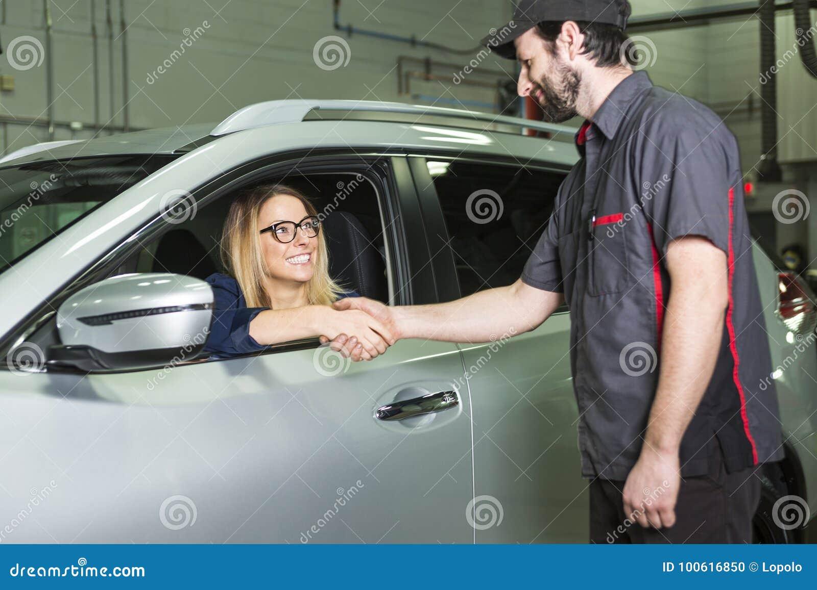 Mecánico de automóviles y cliente femenino en garaje