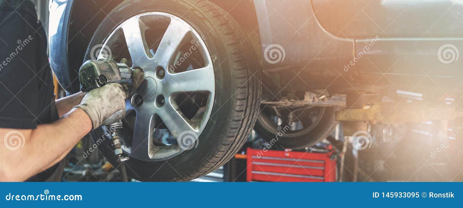 Mecánico de coche que atornilla la rueda en el garaje de la reparación auto