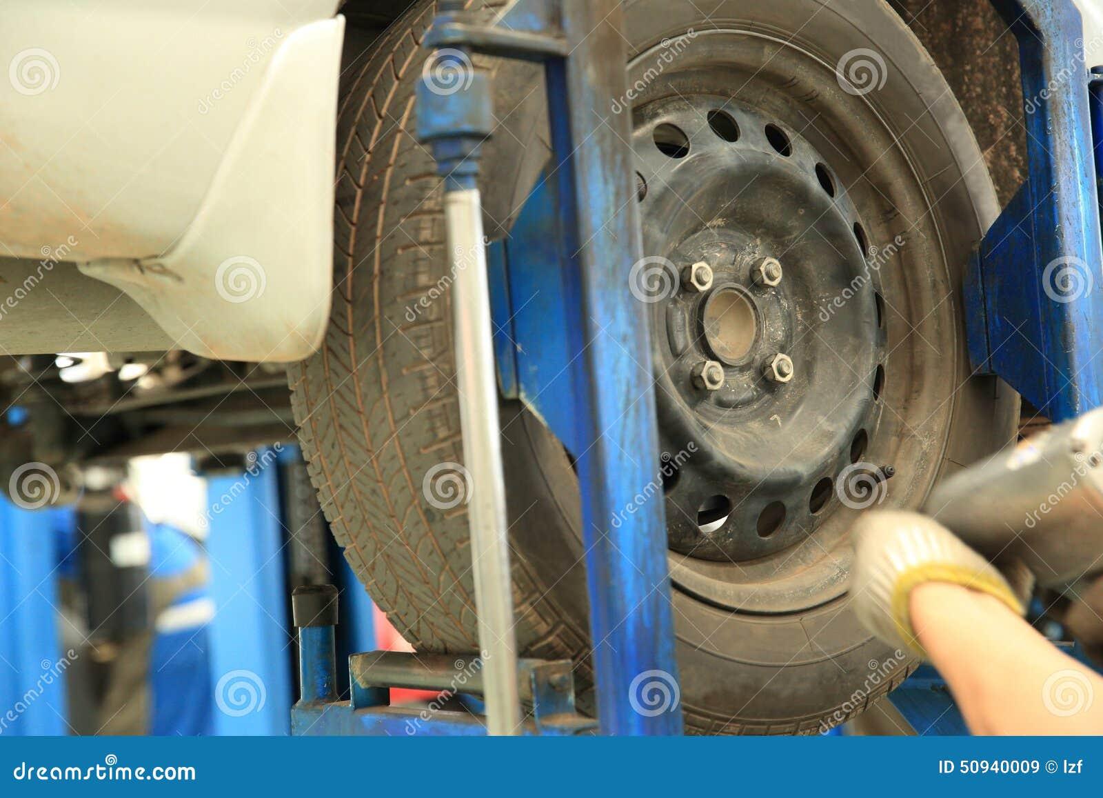 Mecánico de coche que atornilla o que desatornilla la rueda de coche