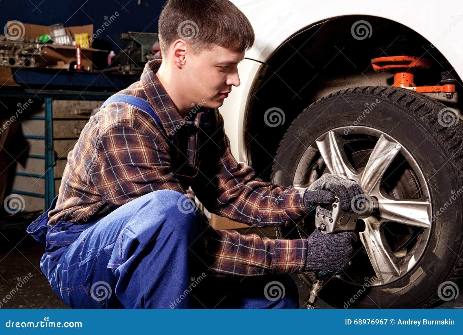 Mecánico de coche que atornilla o que desatornilla la rueda de coche del automobi levantado