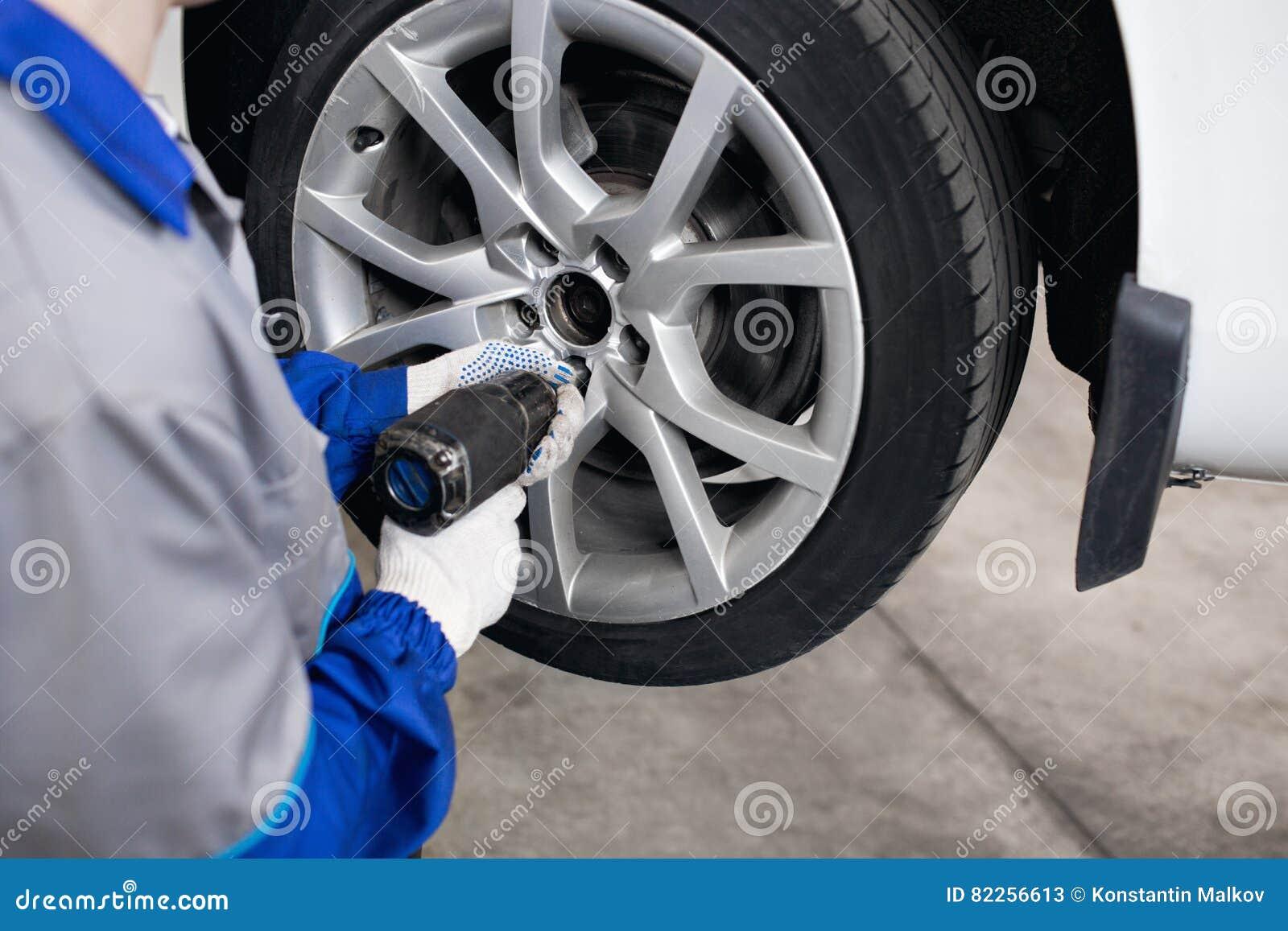 Mecánico de coche que atornilla o que desatornilla la rueda del automóvil levantado por la llave neumática en la gasolinera de la
