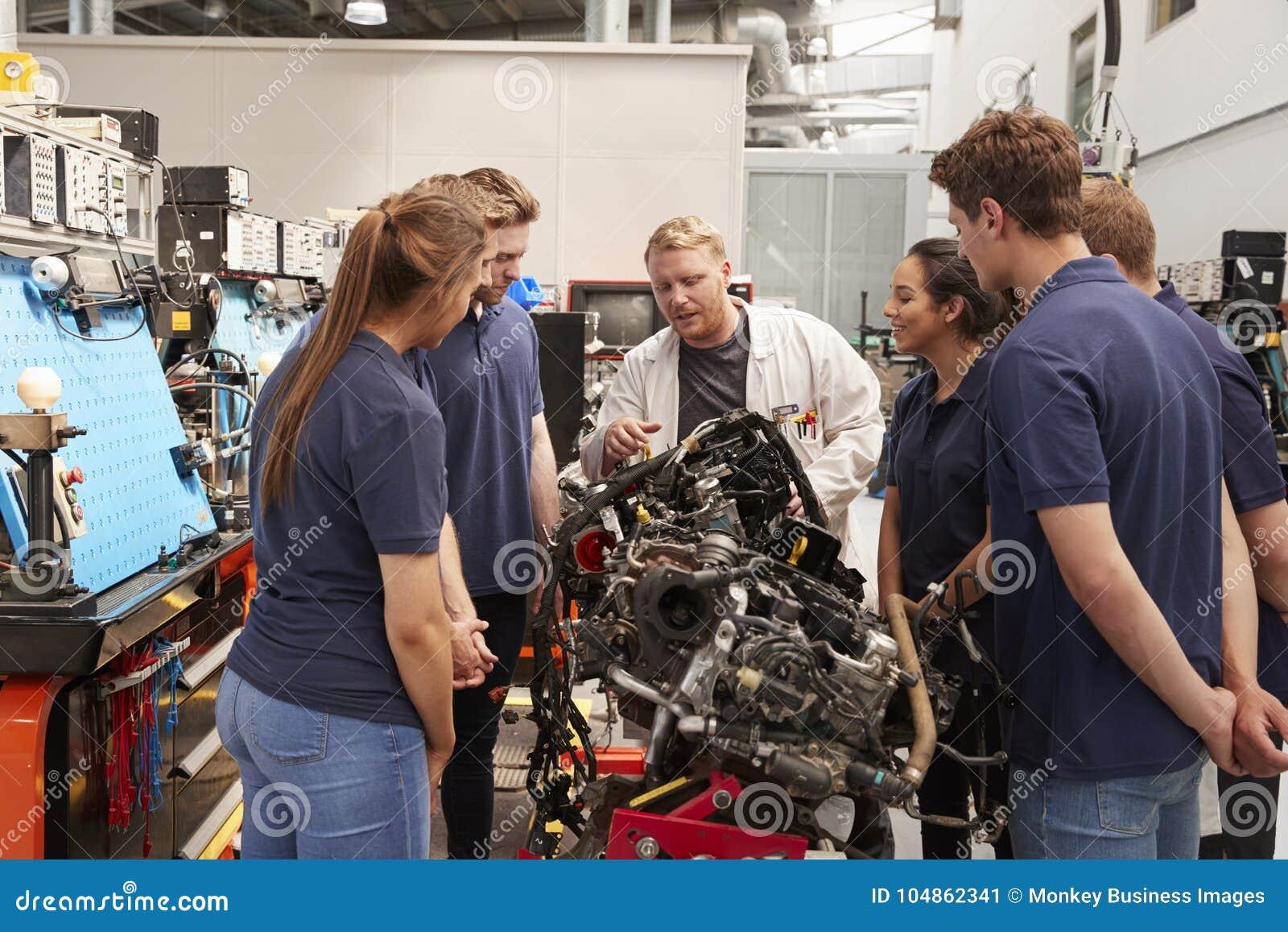 Mecánico de coche que muestra los motores a los aprendices