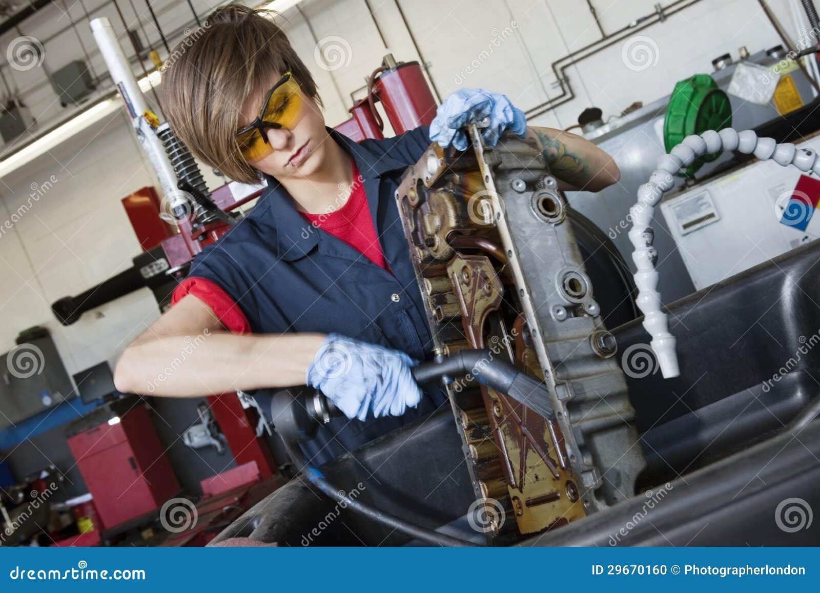 Mecánico de sexo femenino joven que trabaja con el soplete en pieza de maquinaria del vehículo en taller de reparaciones auto