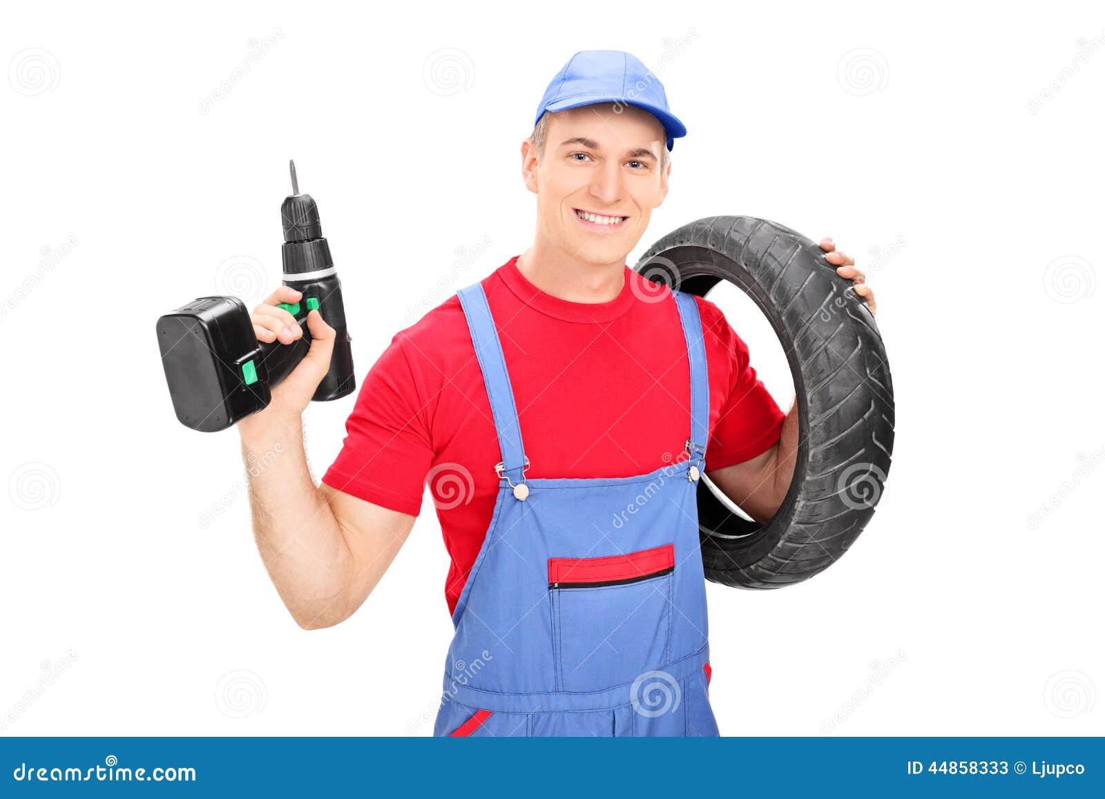 Mecánico de sexo masculino que celebra un neumático y un taladro