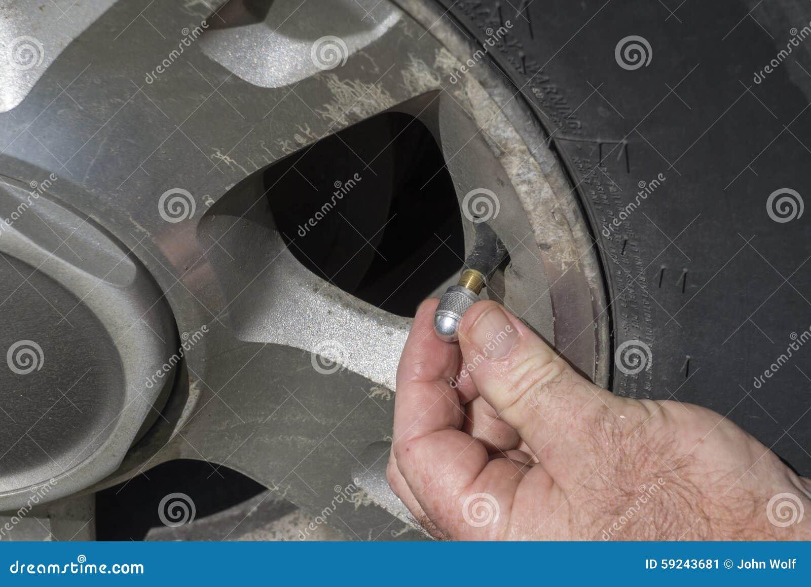 Mecánico Putting On un nuevo casquillo de aluminio del tronco de la válvula de aire