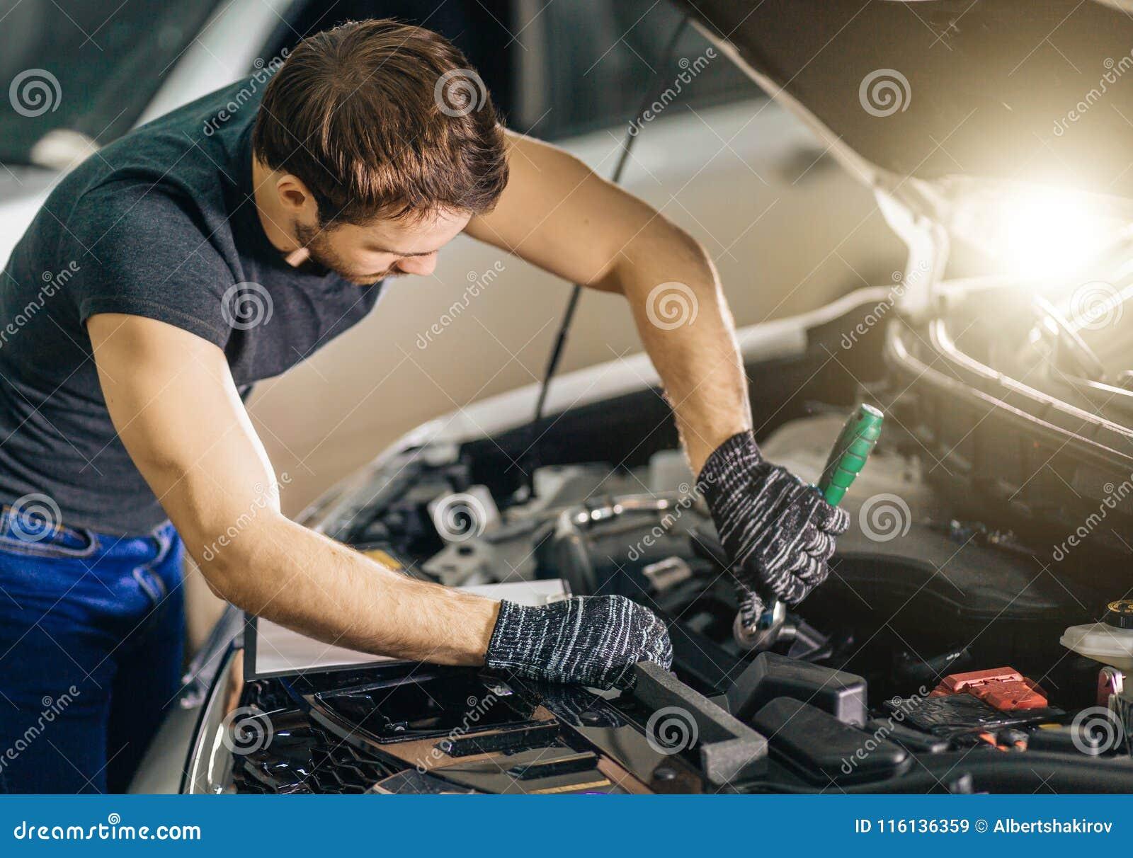 Mecánico que trabaja debajo de la capilla del coche en garaje de la reparación