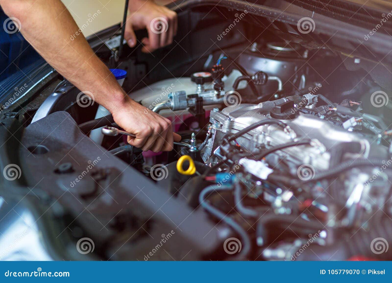 Mecánico que trabaja en el motor de coche en taller de reparaciones auto