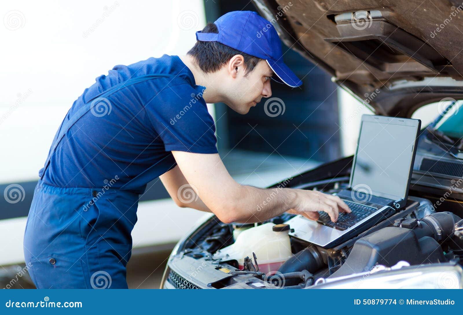 Mecánico que usa un ordenador portátil para comprobar un motor de coche