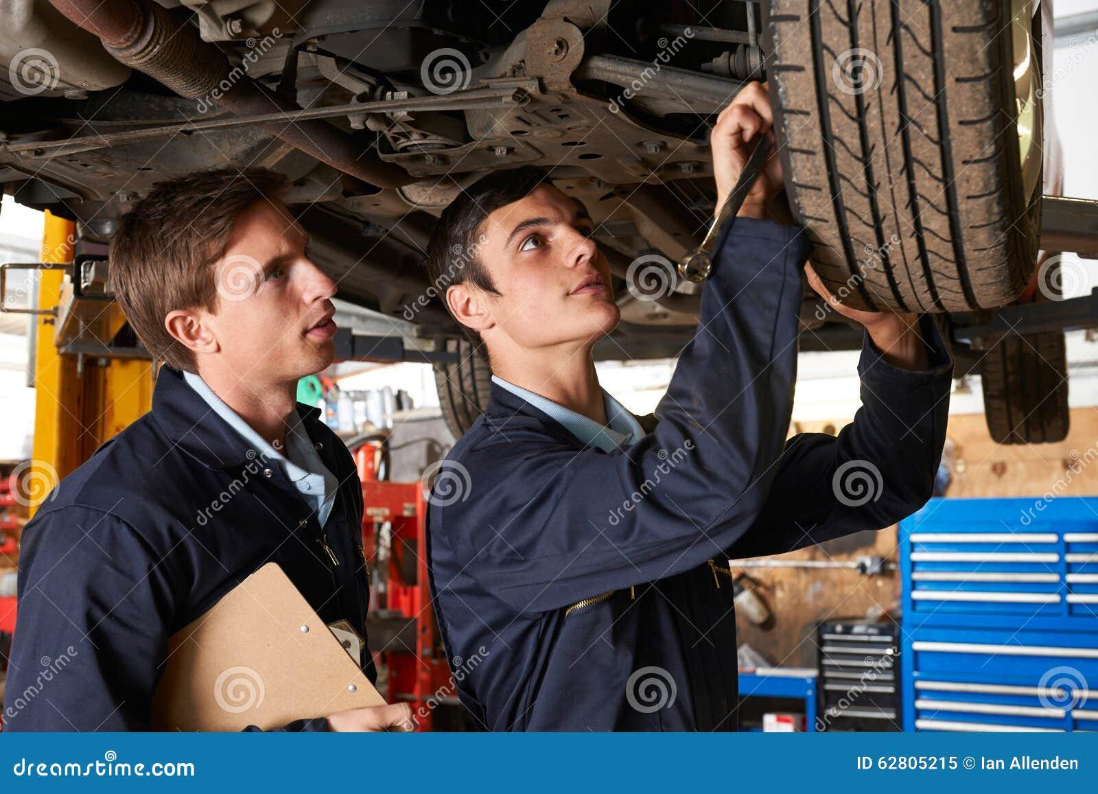 Mecánico And Trainee Working en el coche junto