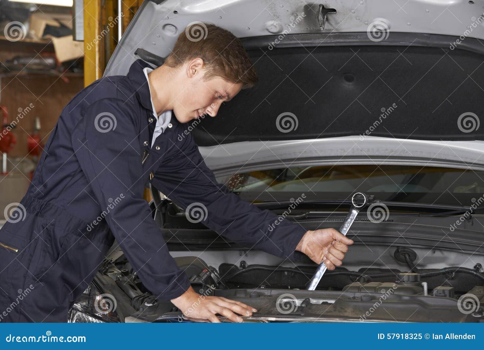 Mecânico In Auto Shop do aprendiz que trabalha no motor de automóveis