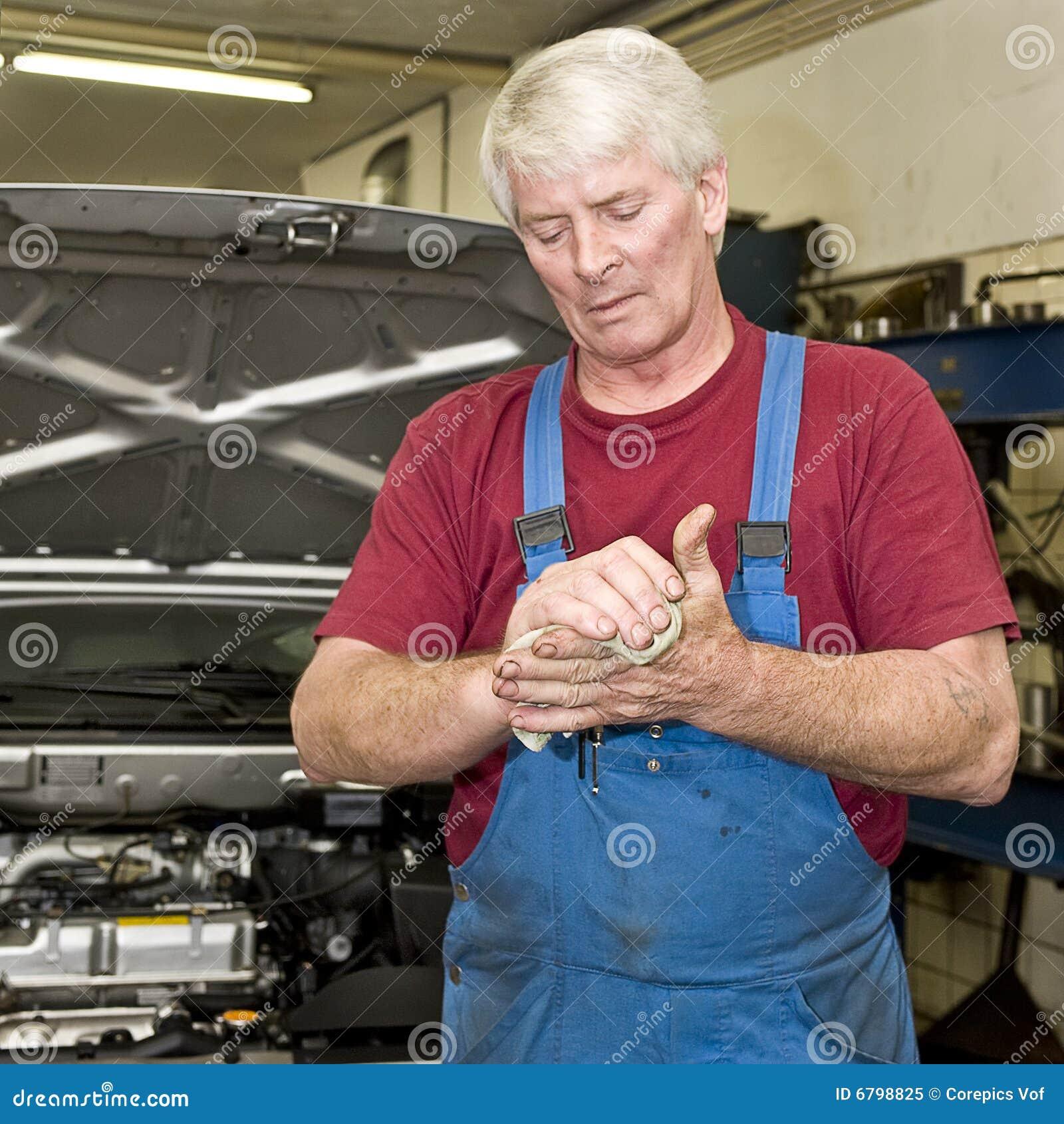 Mecânico de carro que limpa suas mãos
