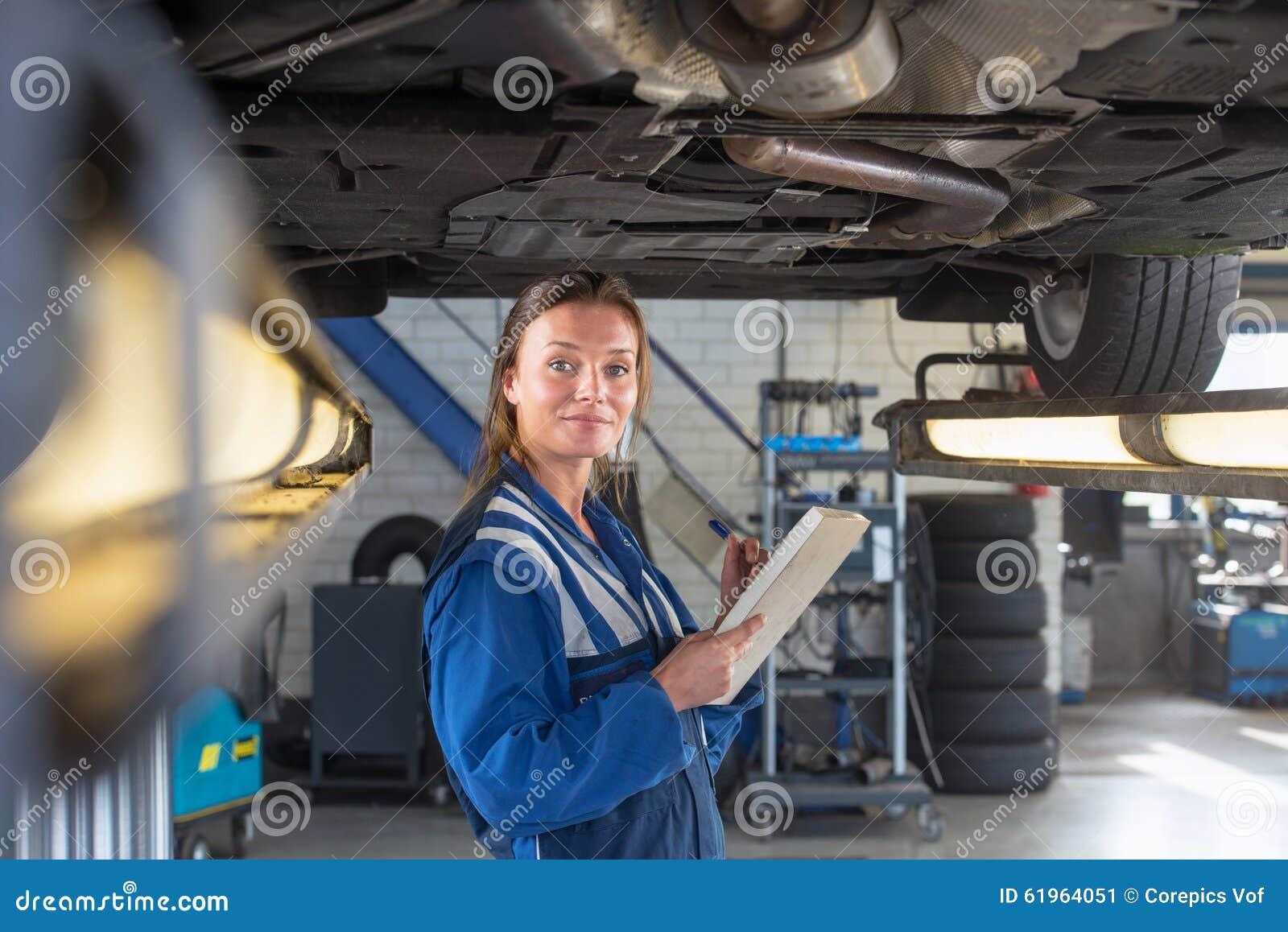 Mecânico debaixo de um carro durante um exame periódico
