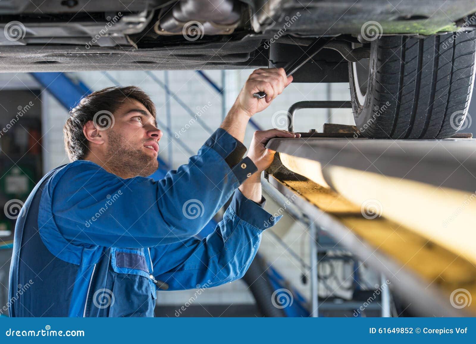 Mecânico que examina a suspensão de um carro durante um teste de MOT