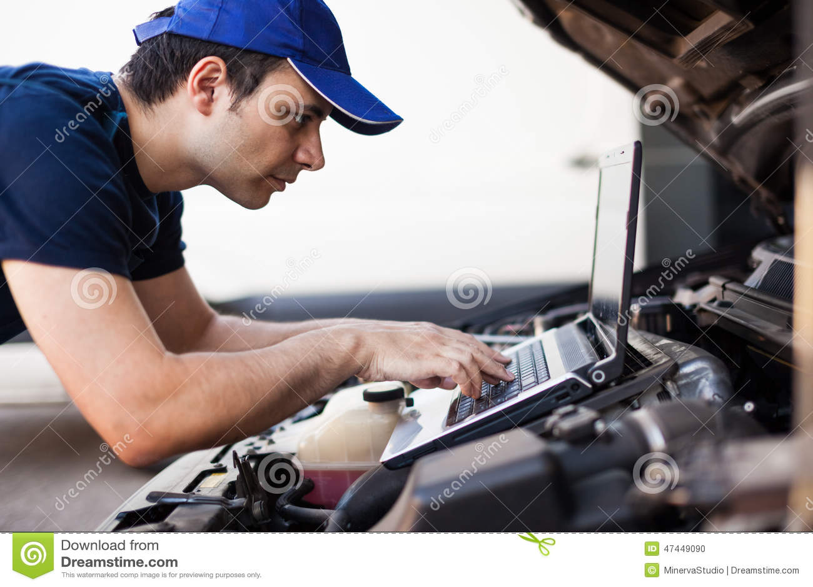 Mecânico que usa um laptop para verificar um motor de automóveis