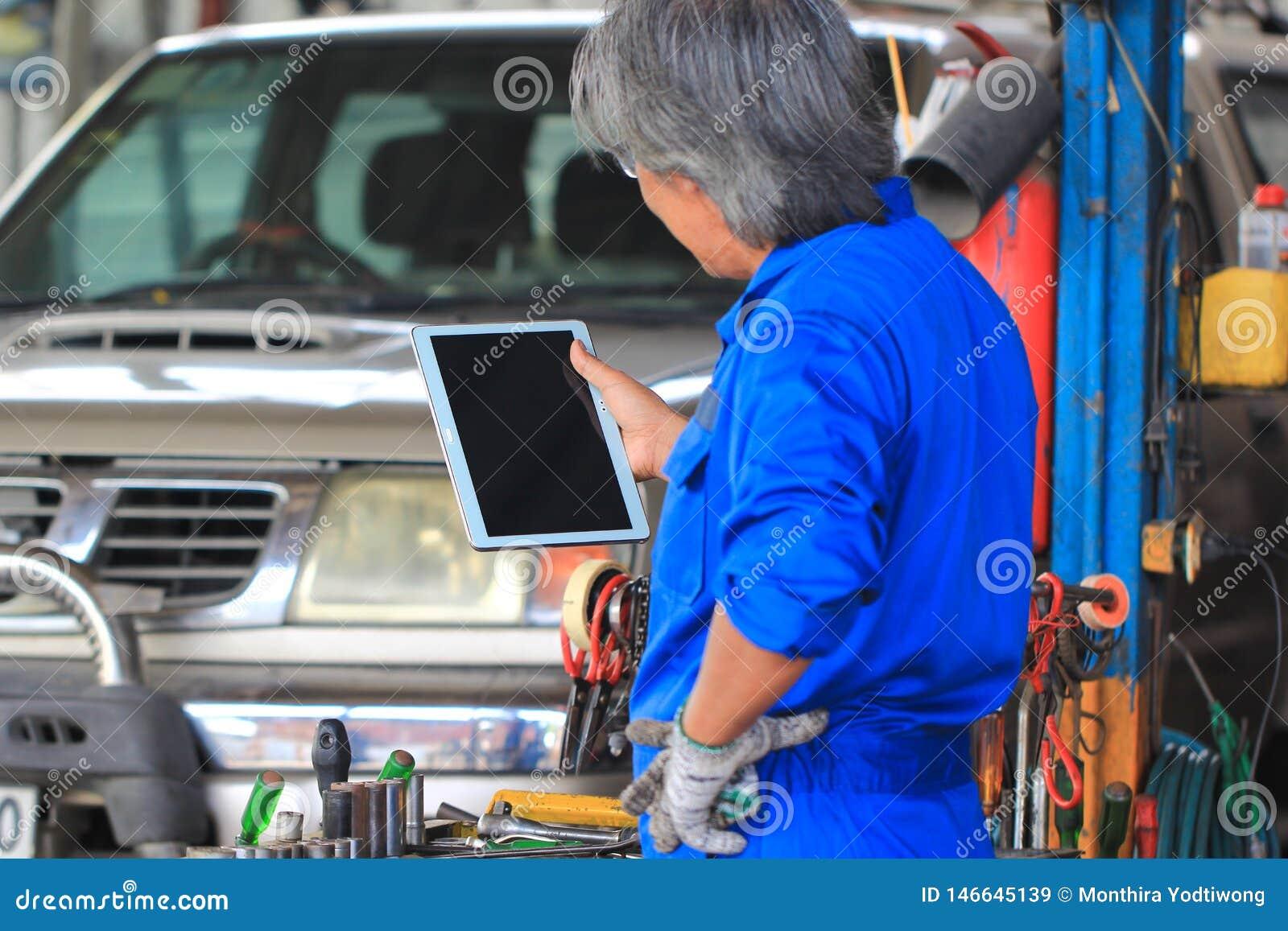 Mec?nico de carro que guarda a tabuleta digital no servi?o de repara??o de autom?veis