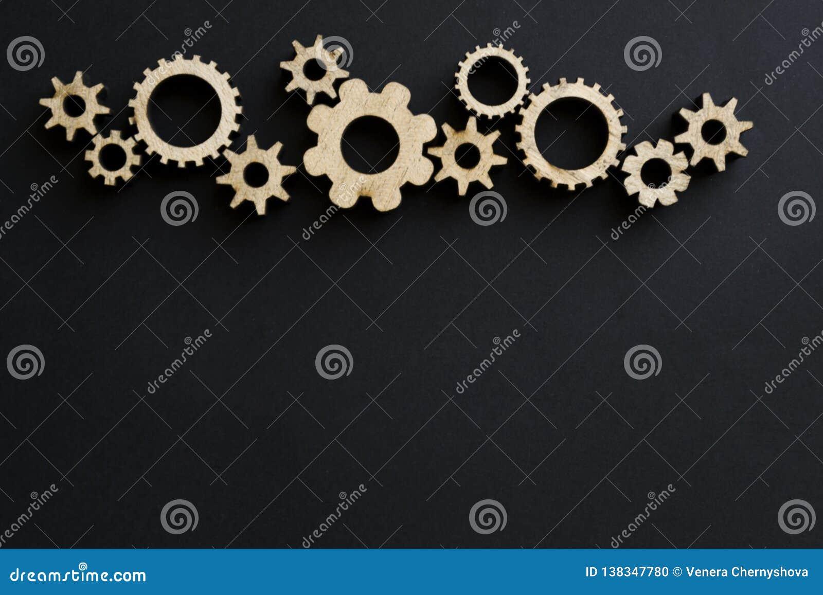 Mecanismos de madeira em um fundo preto Placa de giz preta