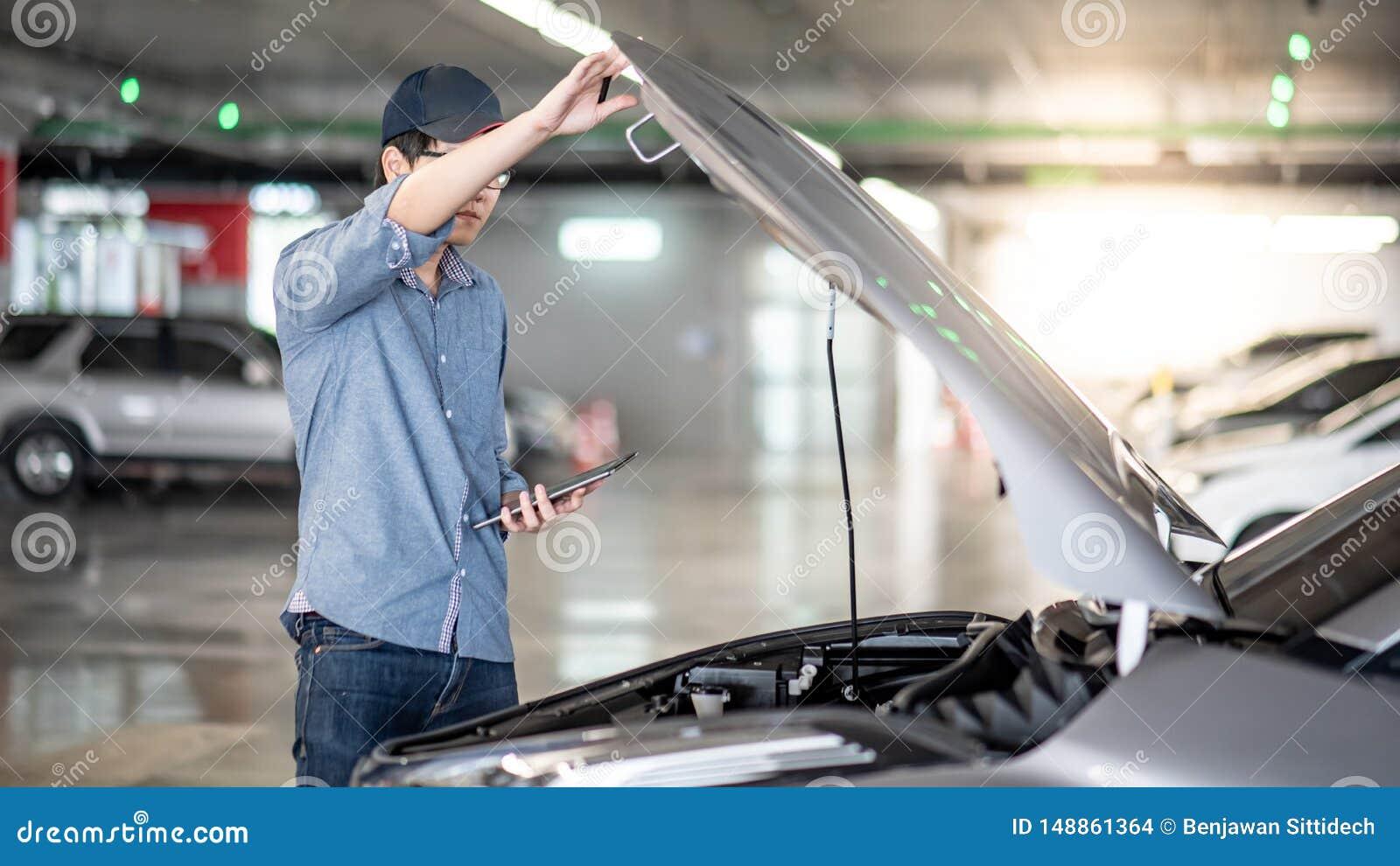 Meccanico asiatico che controlla l automobile facendo uso della compressa