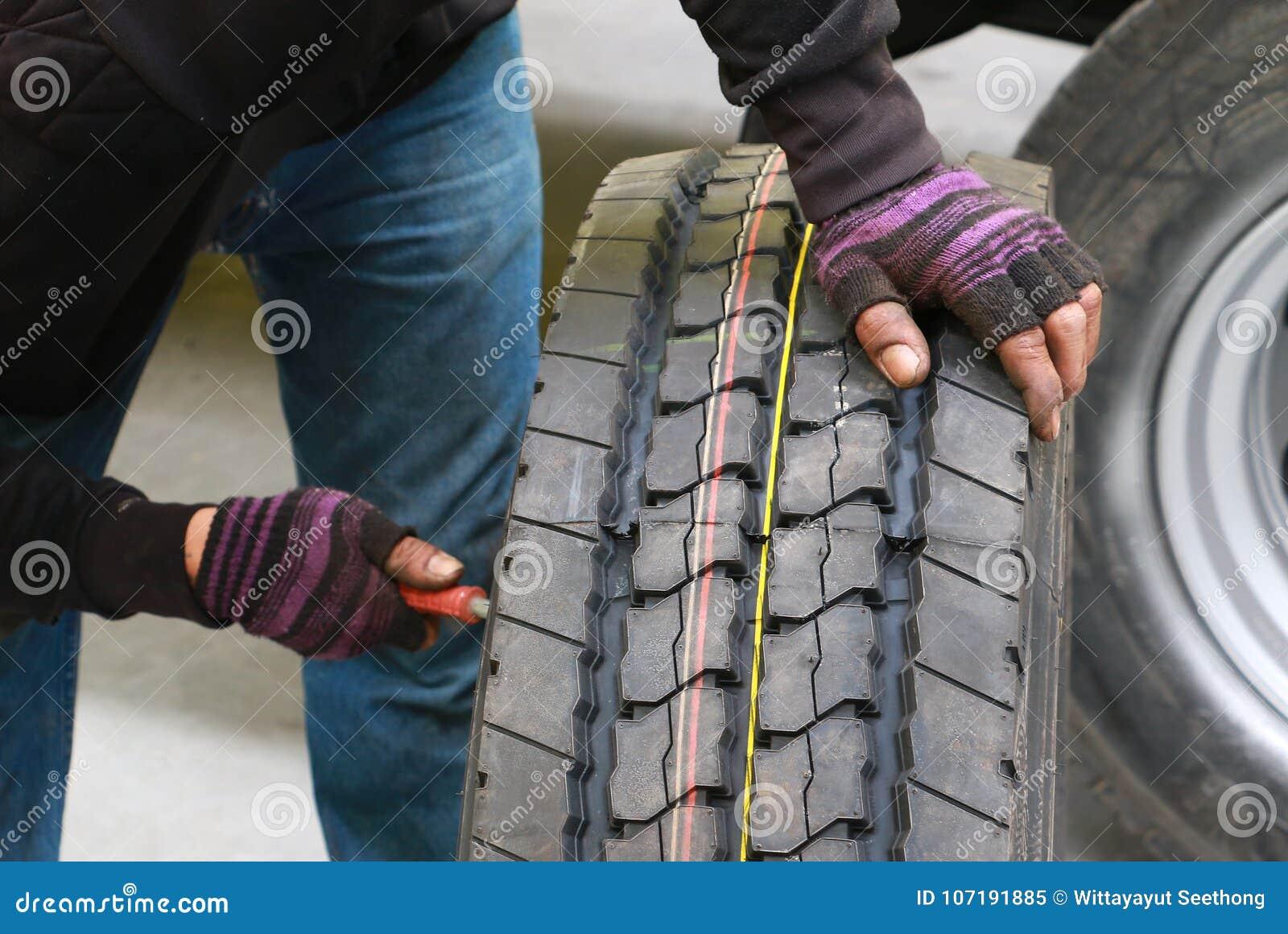 Meccanico asiatico dell uomo che cambia una ruota di un camion dell automobile in officina Il camion cambiante del meccanico spin