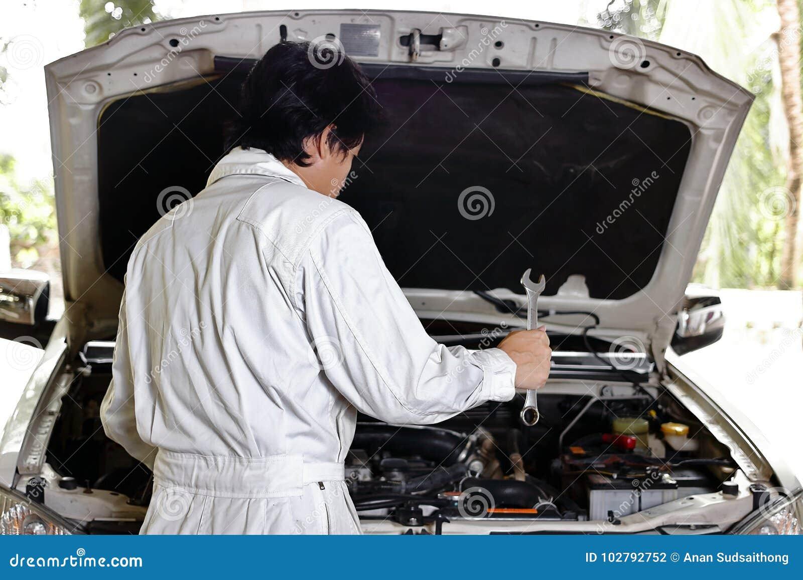 Meccanico automobilistico in uniforme con la chiave che diagnostica motore sotto il cappuccio dell automobile al garage di ripara