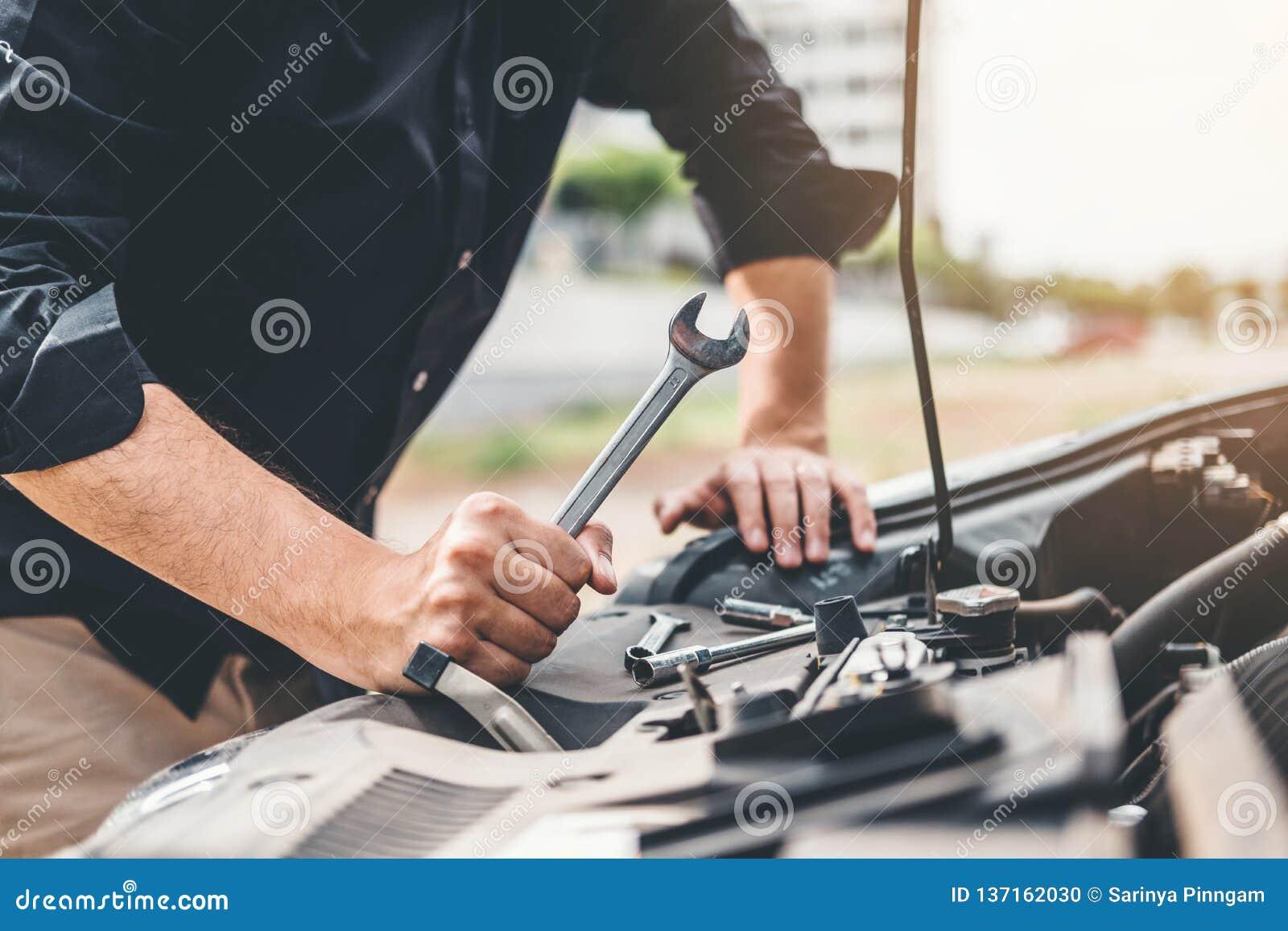 Meccanico che lavora nel tecnico Hands del garage del meccanico di automobile che lavora in controllo di automobile di servizio e