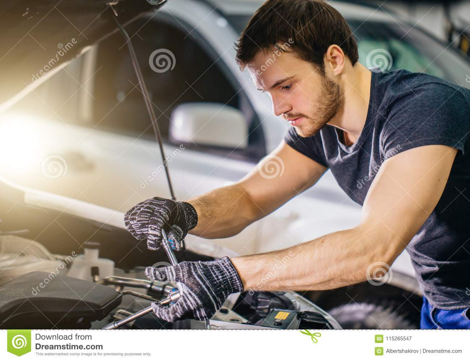 Meccanico che lavora sotto il cappuccio dell automobile nel garage di riparazione