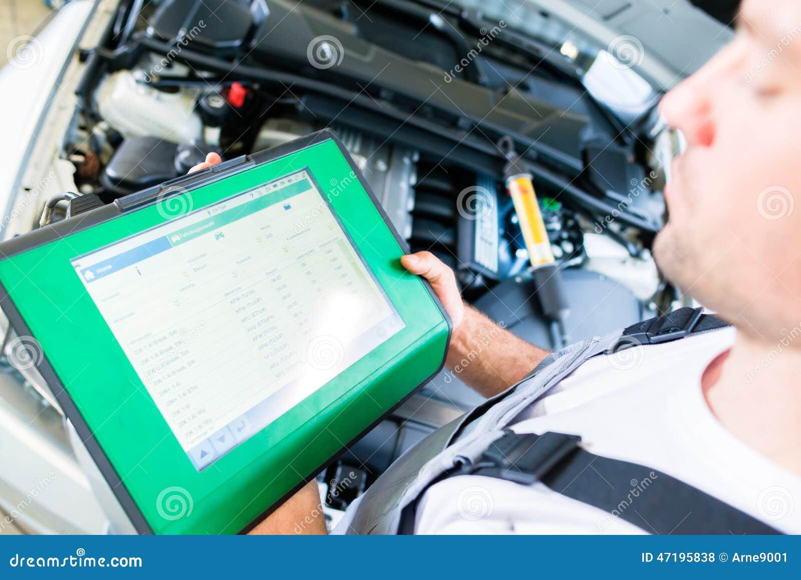 Meccanico con lo strumento diagnostico nell officina dell automobile