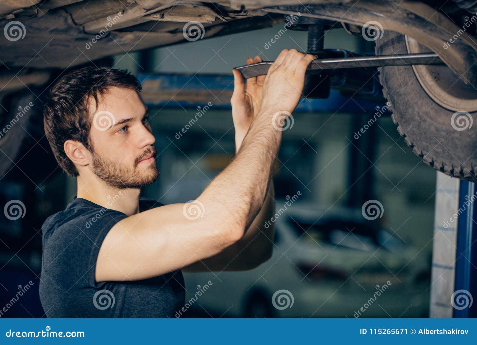 Meccanico sotto l automobile nella gomma examing del garage e nello stato tecnico