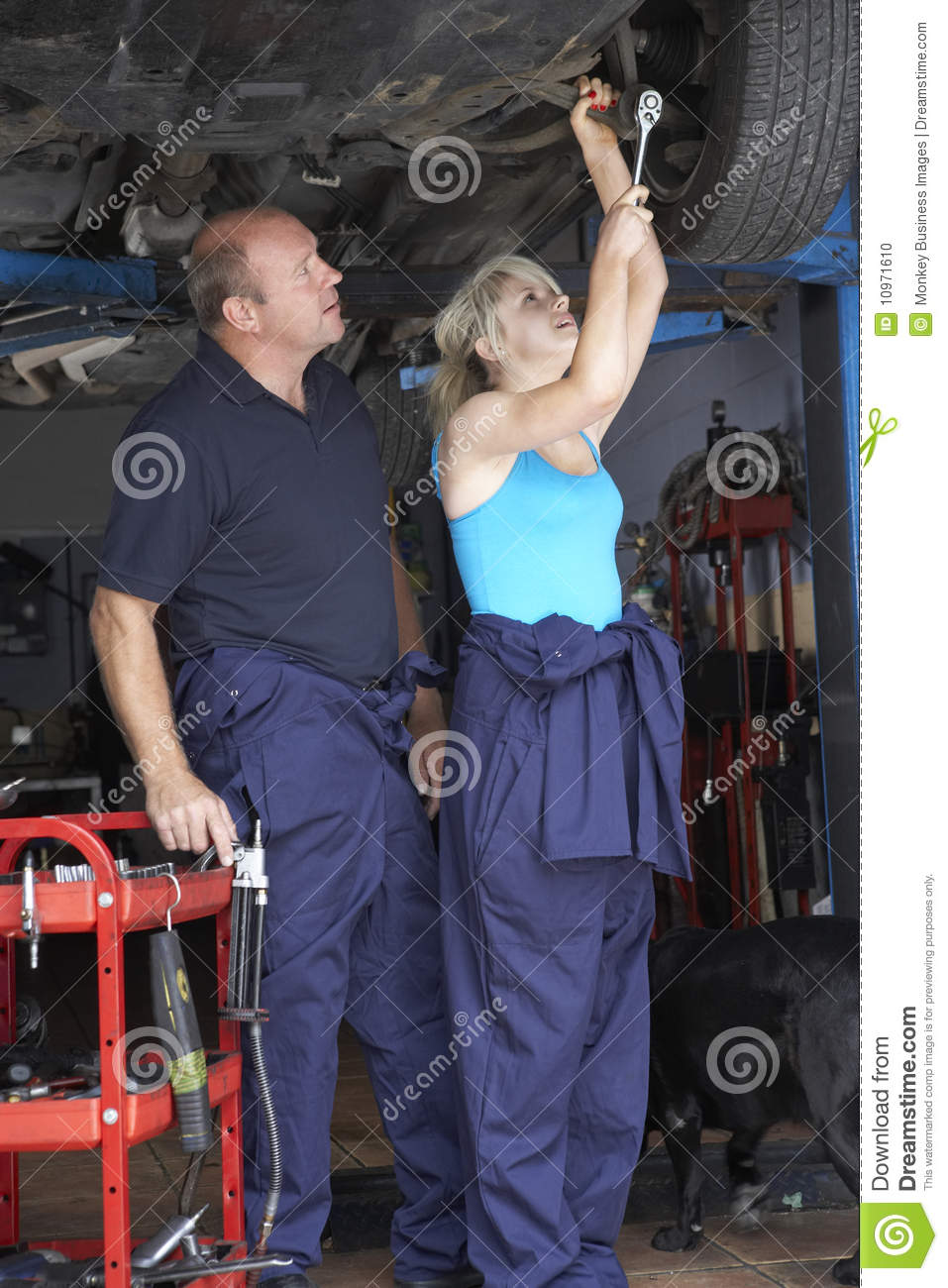 mechanic and apprentice working on car stock photo
