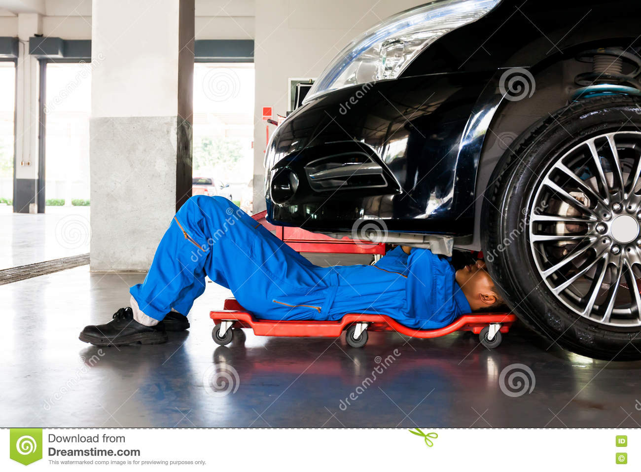 Mechanic in blue uniform lying down and working under car for Garage auto 7