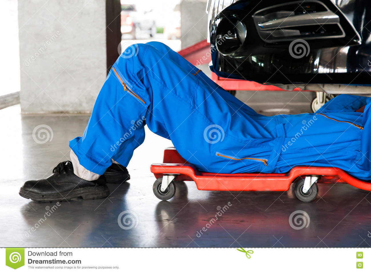 mechanic in blue uniform lying down and working under car at aut stock image image 73986239. Black Bedroom Furniture Sets. Home Design Ideas