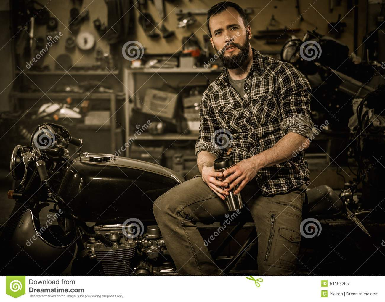 Mechanic building vintage style cafe-racer motorcycle