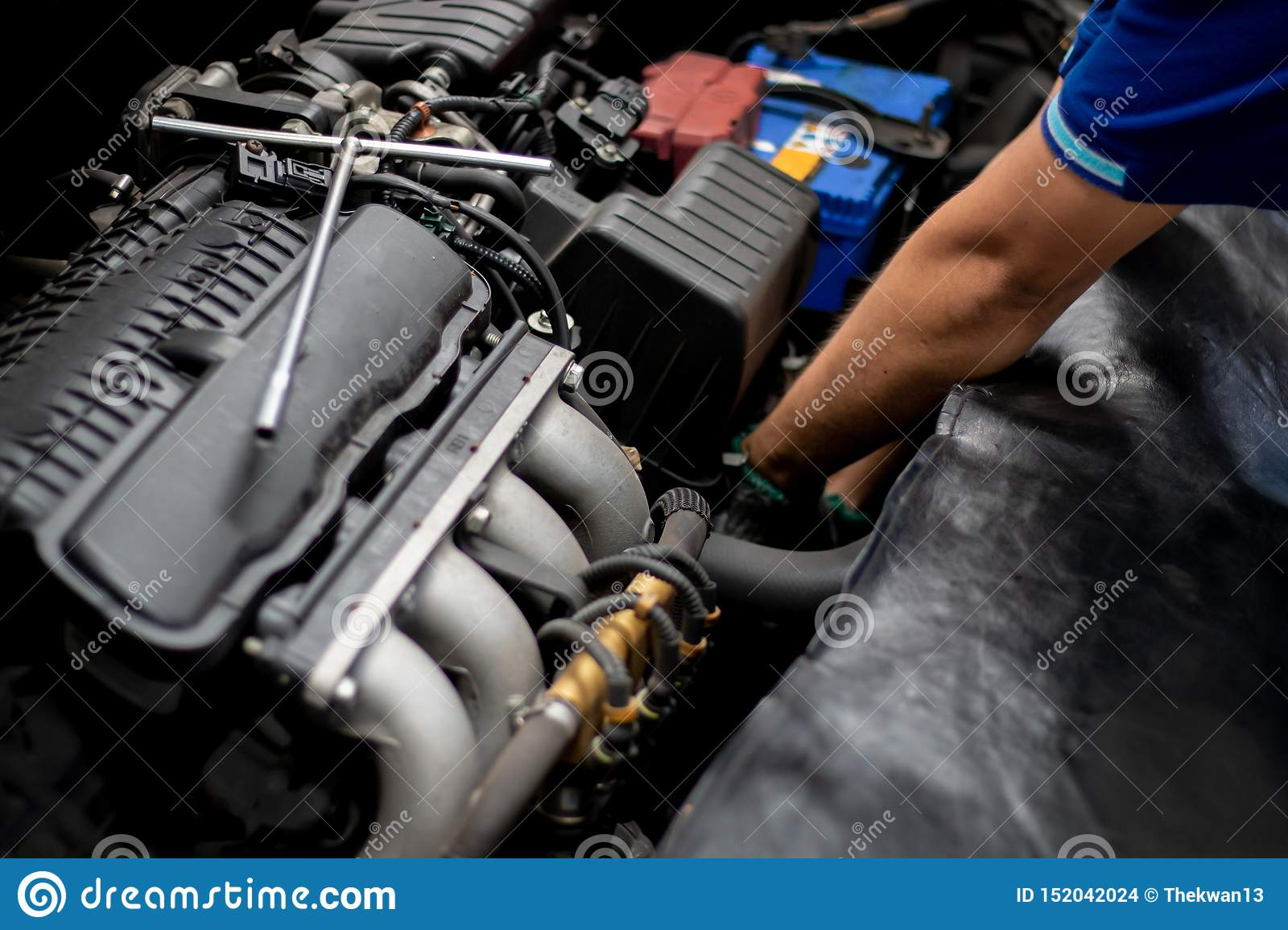 Mechanic checking the car engine in auto repair