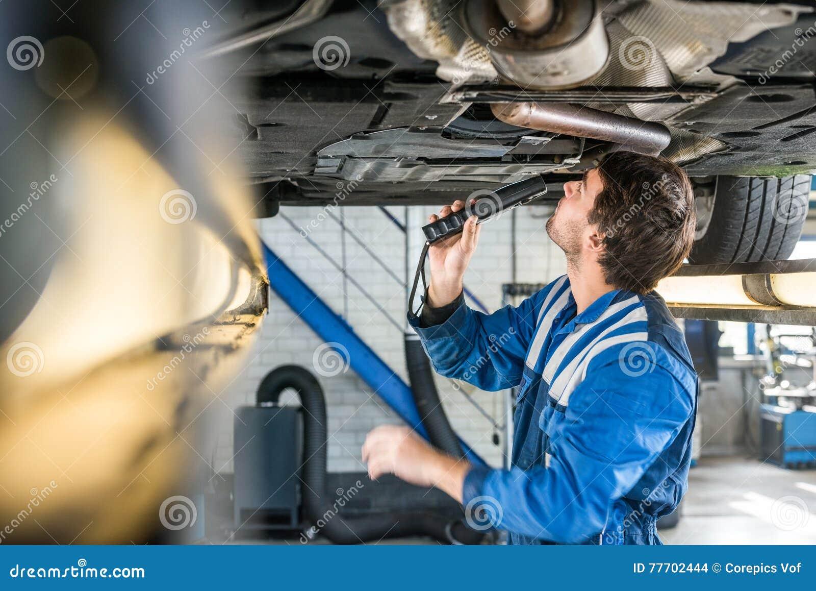 mechanic with flashlight examining under the car stock photo image