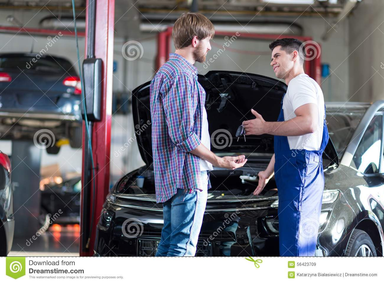 car mechanic giving client keys to his repaired car in auto repair service stock photo. Black Bedroom Furniture Sets. Home Design Ideas