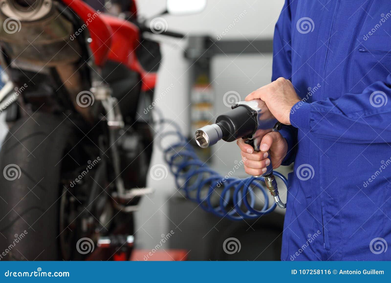 Mechanic hand holding a pneumatic gun