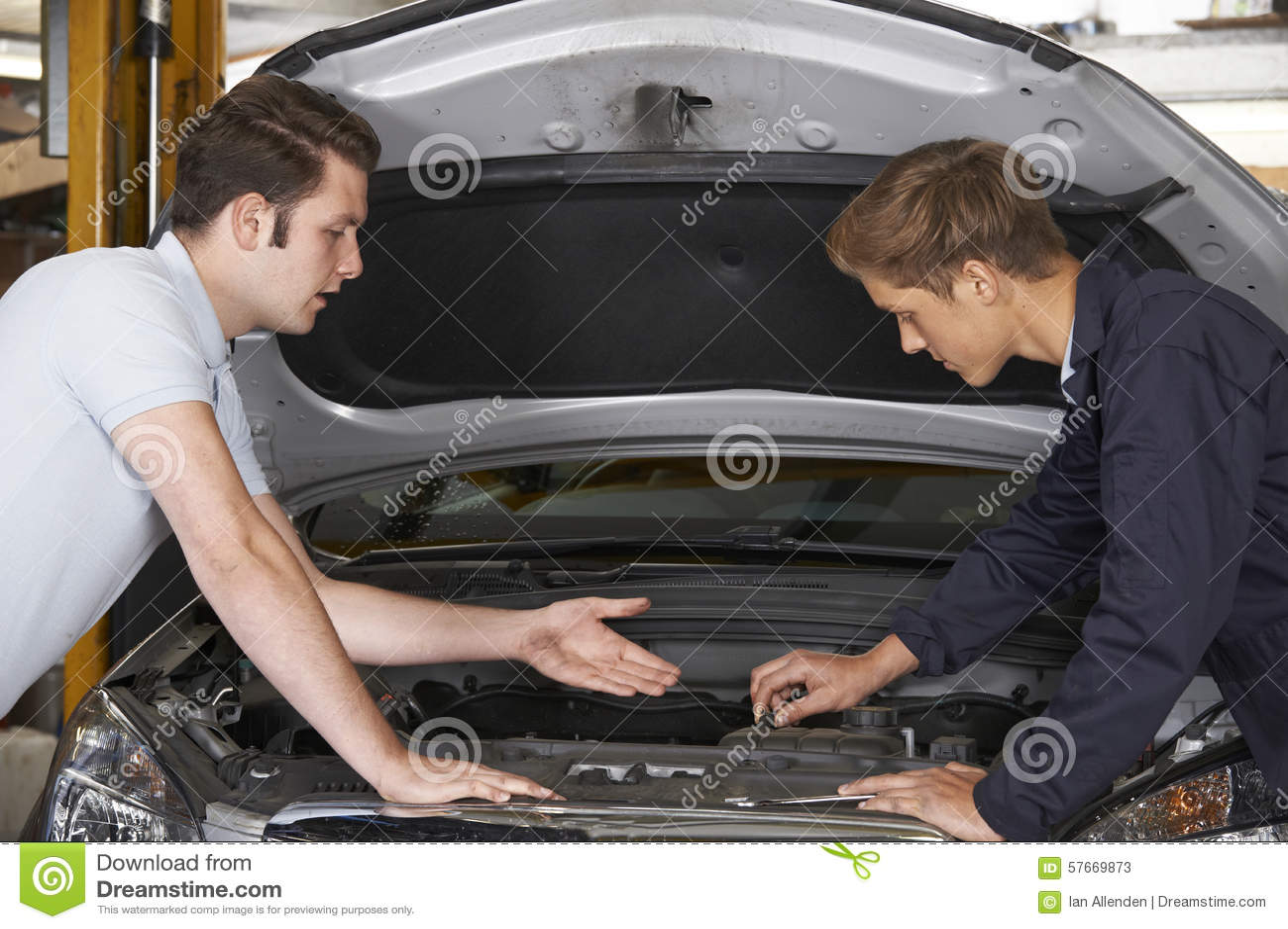 Mechanic Helping Apprentice To Fix Engine