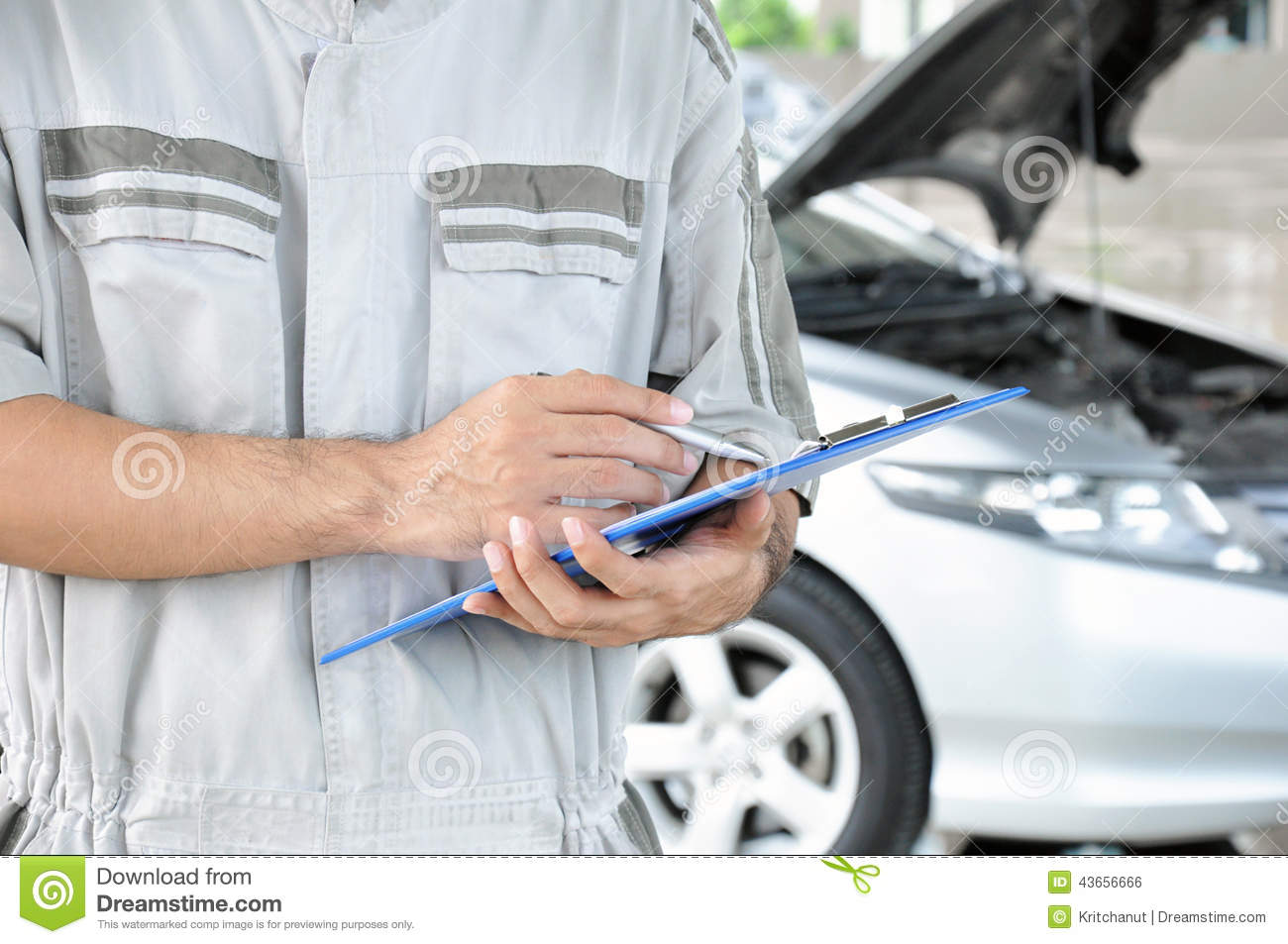 A mechanic holding clipboard in front of car engine