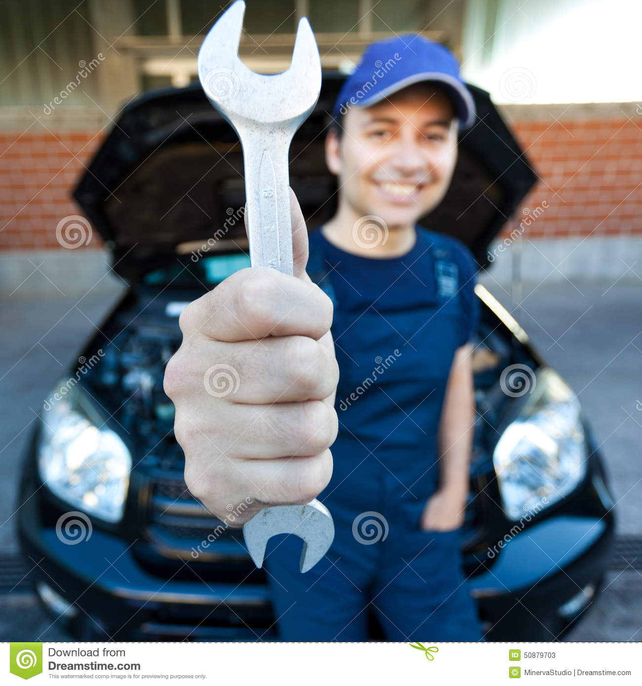 Mechanic holding a wrench at a car garage