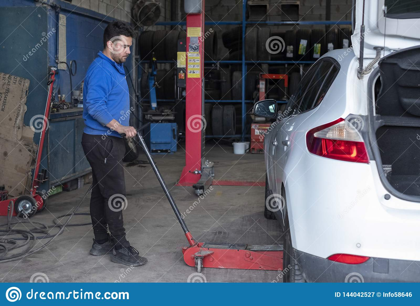 Mechanic lifting car with a hydraulic jack in a workshop