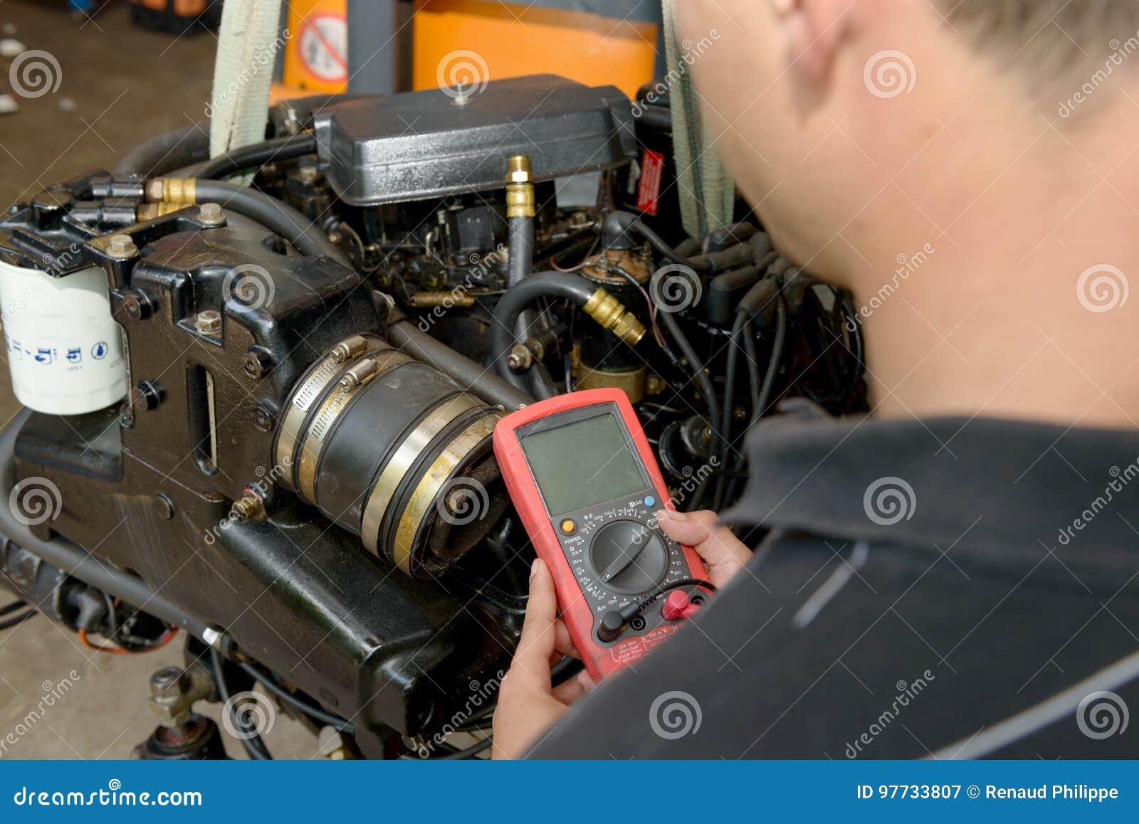 Automotive Digital Multimeter : Mechanic man with digital multimeter testing ignition coil stock