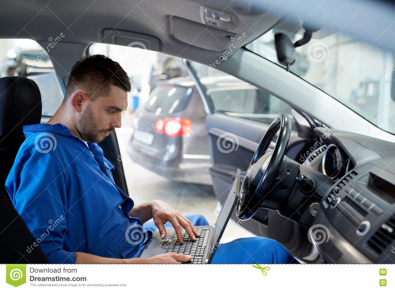 Mechanic man with laptop making car diagnostic
