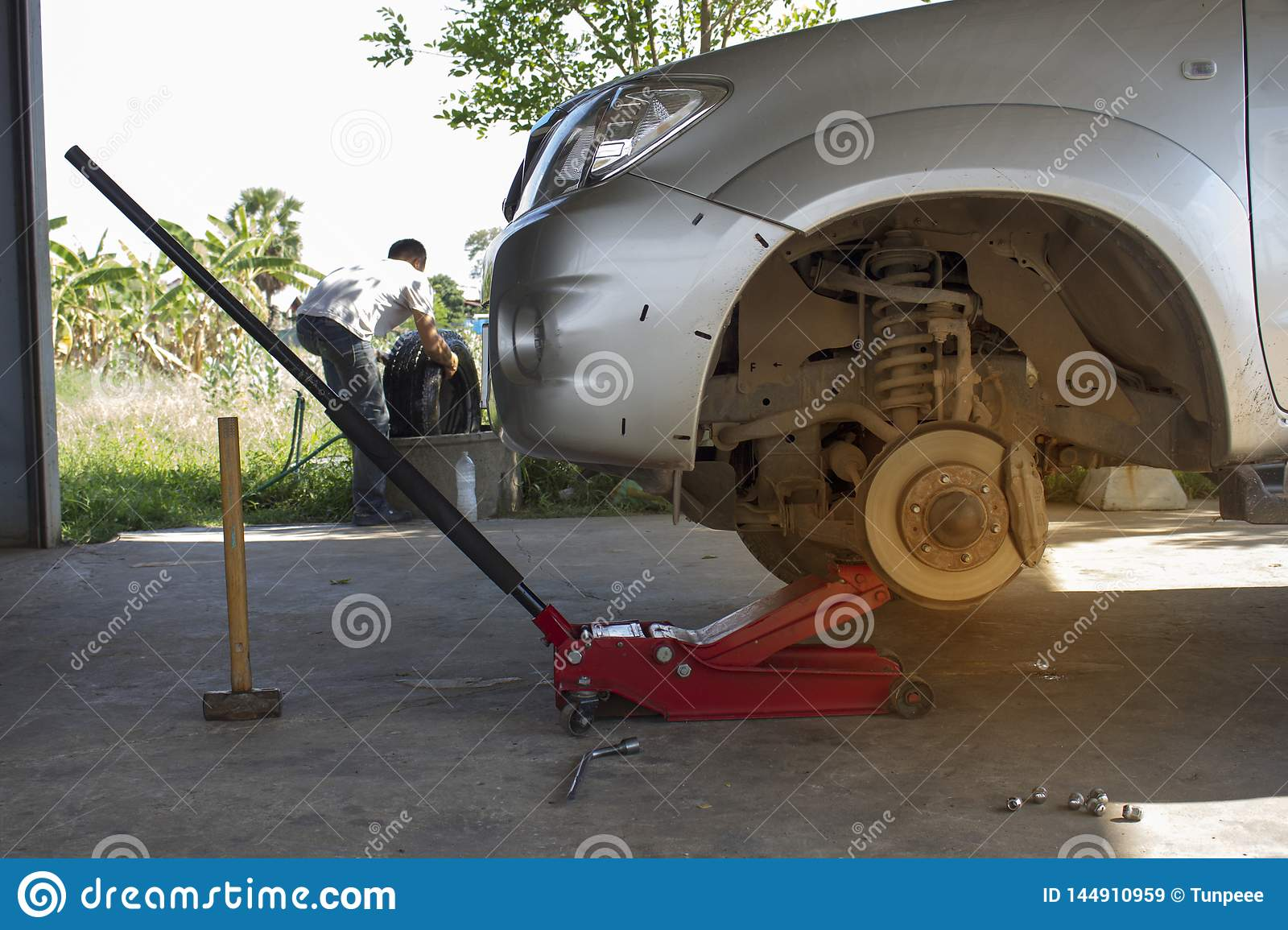 The mechanic is removing the pickup truck tires using the red jack