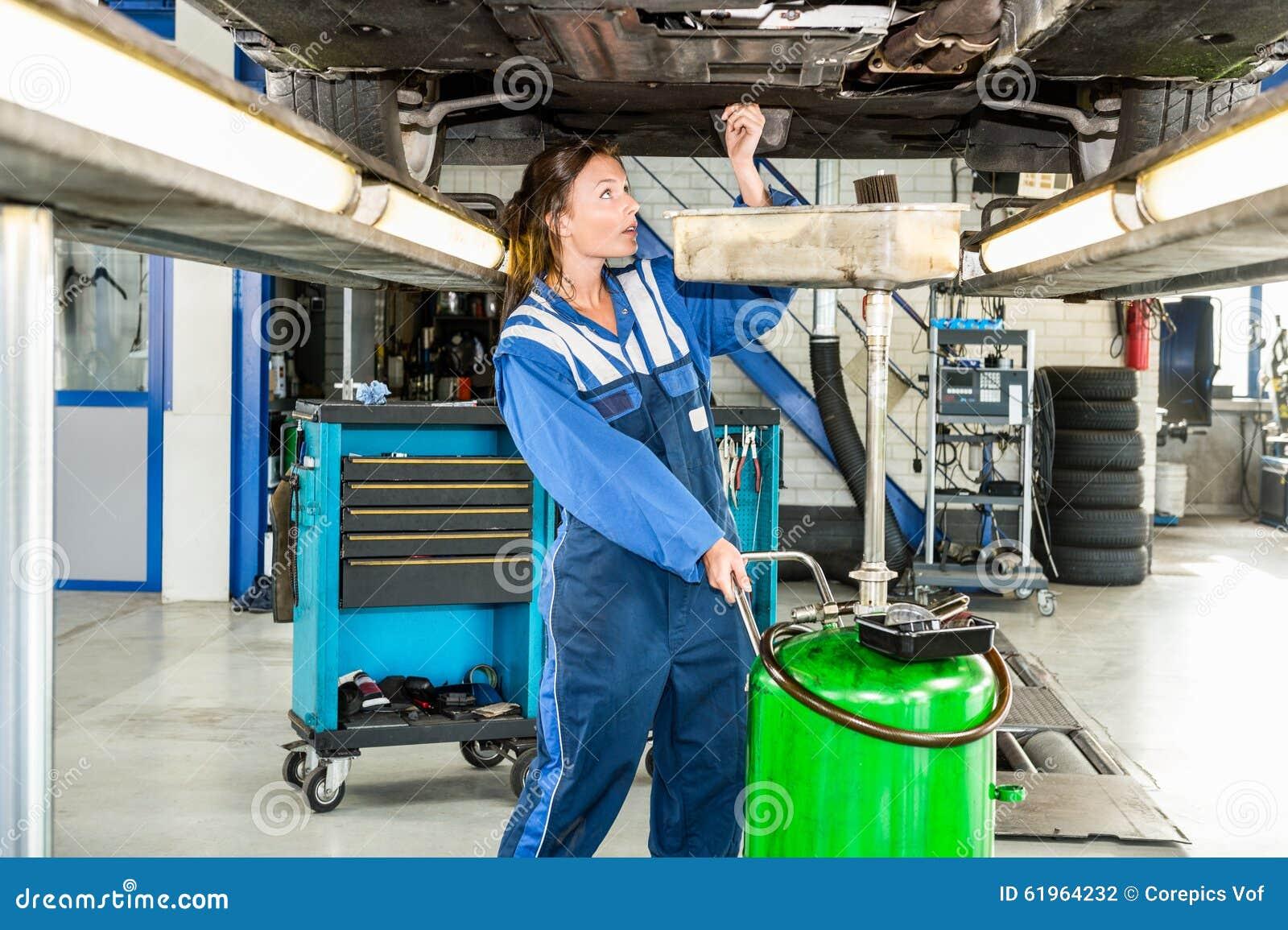 mechanic repairing car on hydraulic lift stock photo