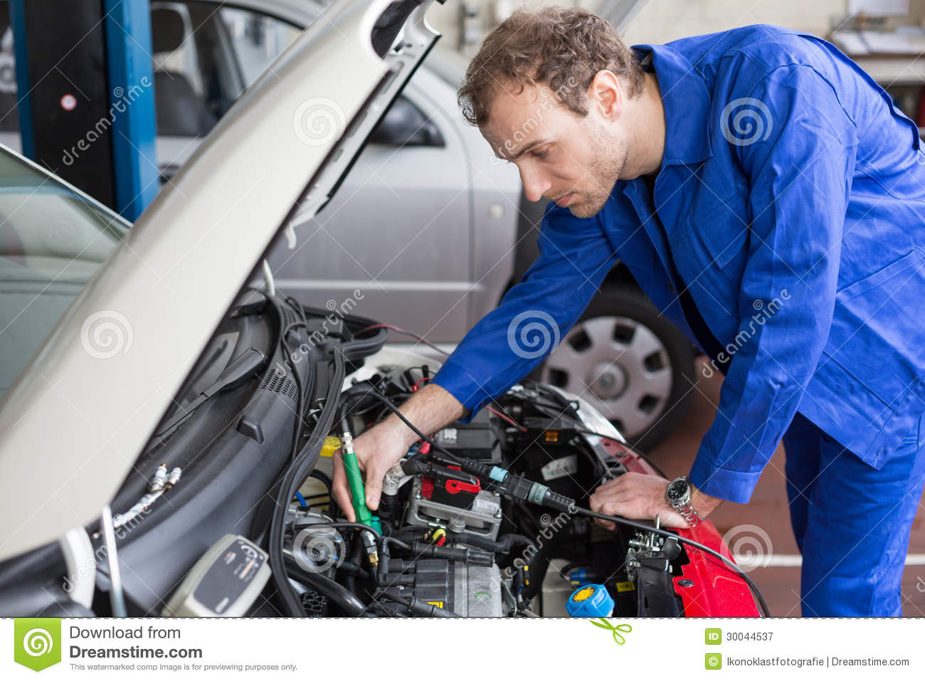 Mechanic repairing a car in a workshop or garage royalty for Electric motor parts near me