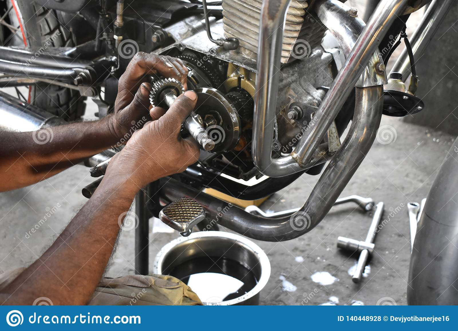 A mechanic repairing motor bike,maintenance, technical