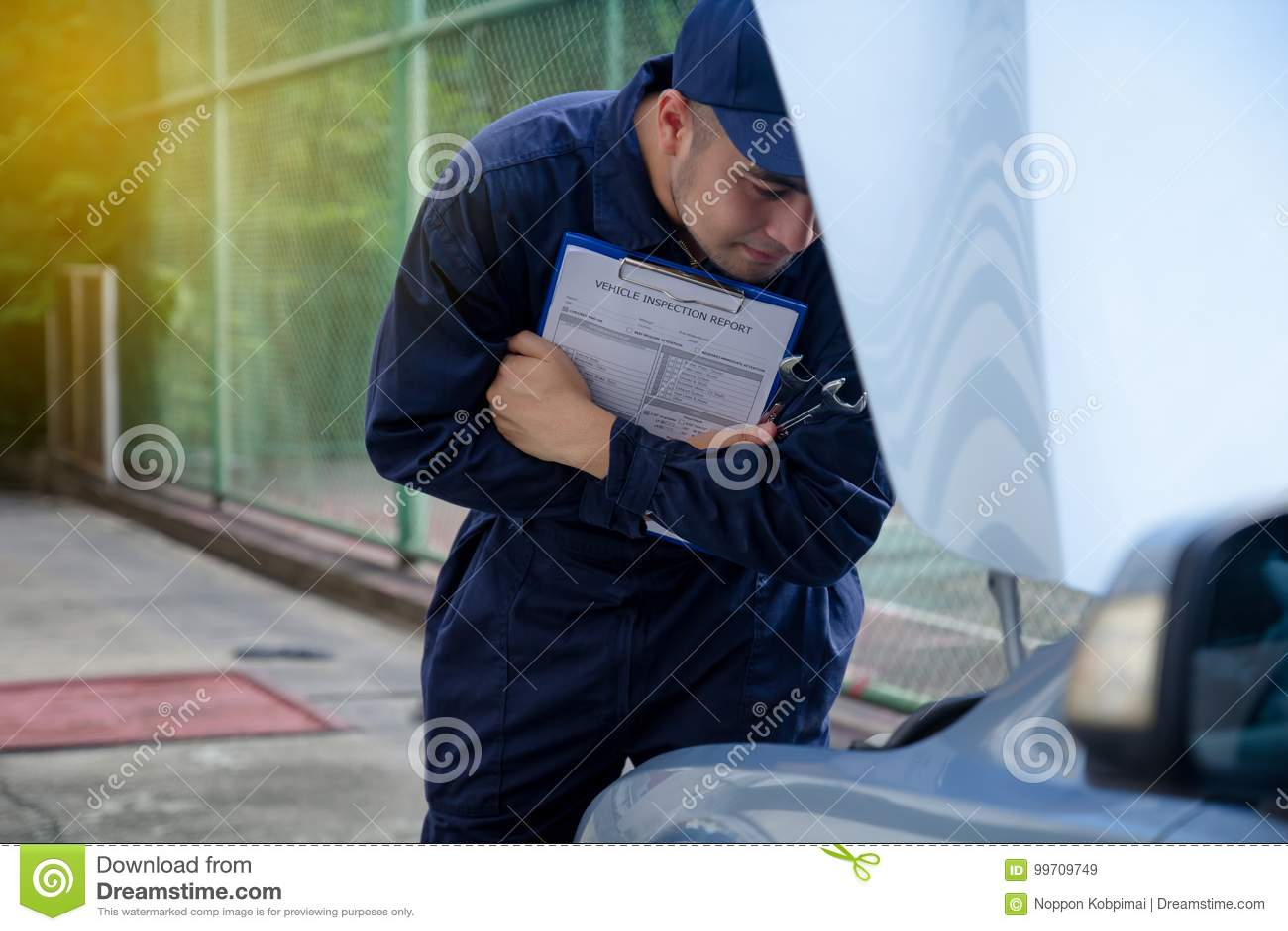 mechanic repairman inspecting car maintaining car records stock
