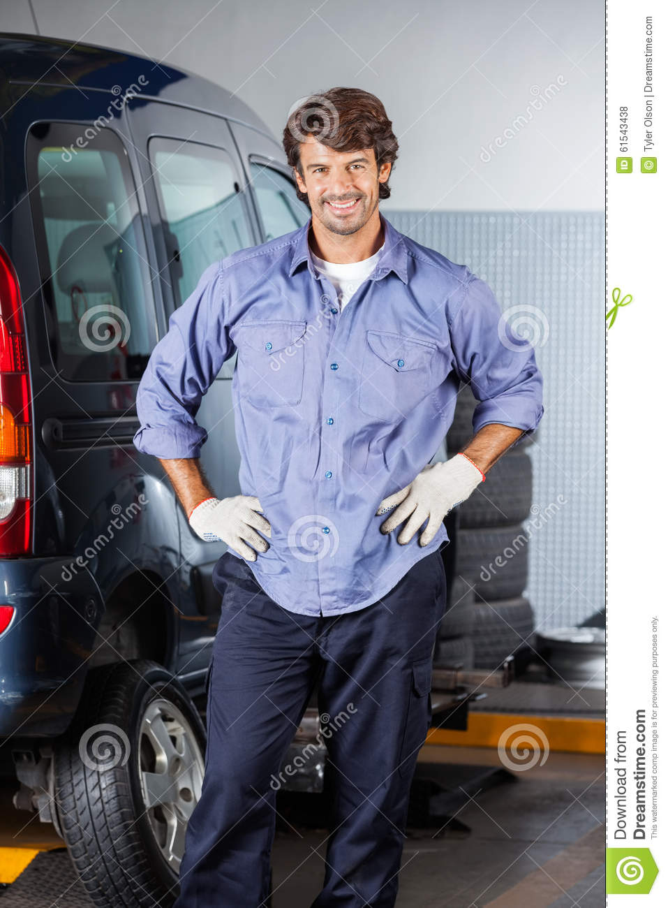 Hands On Garage : Mechanic standing with hands on hip by car stock photo