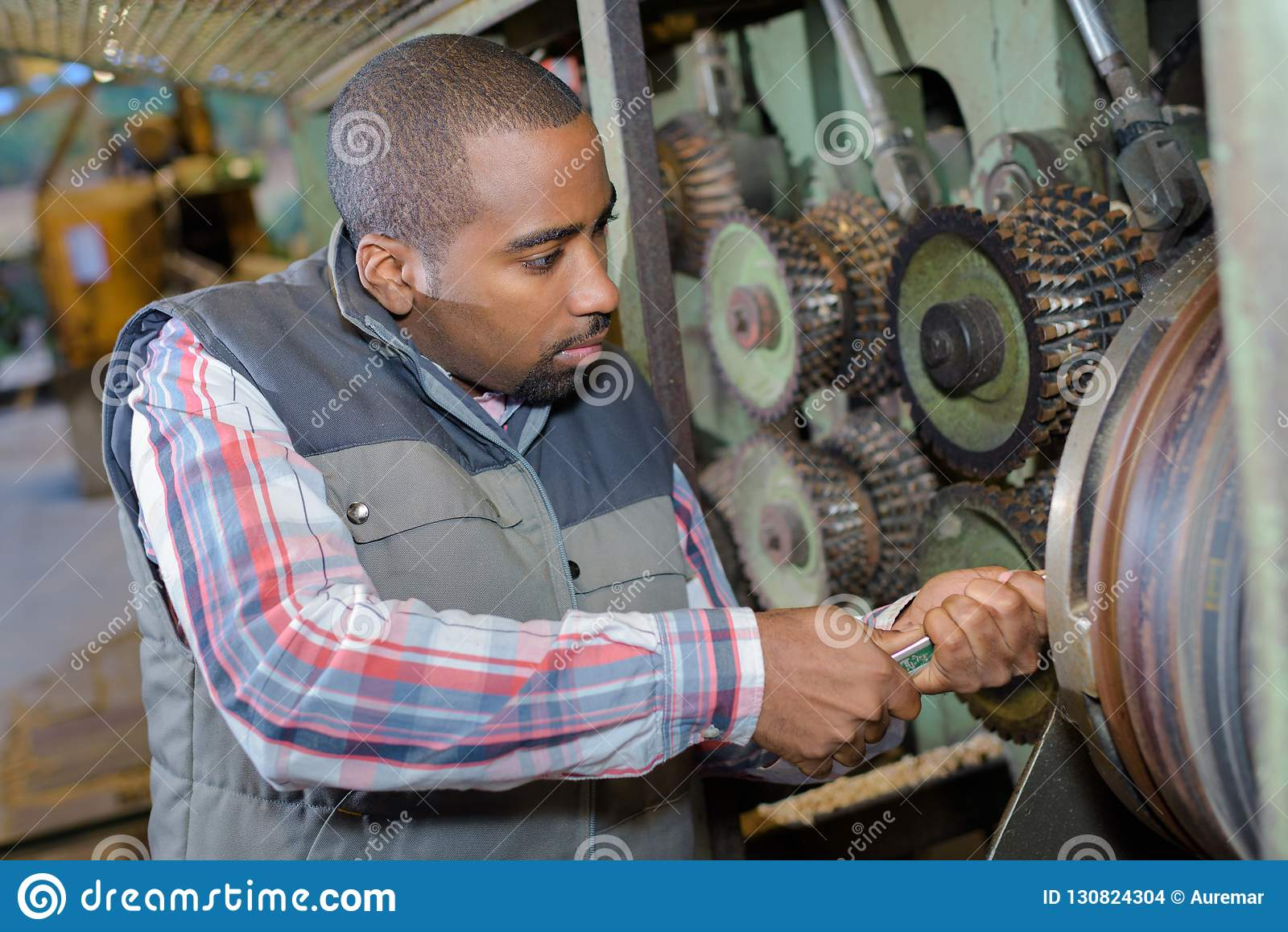 Mechanic using effort to tuen spanner on machinery